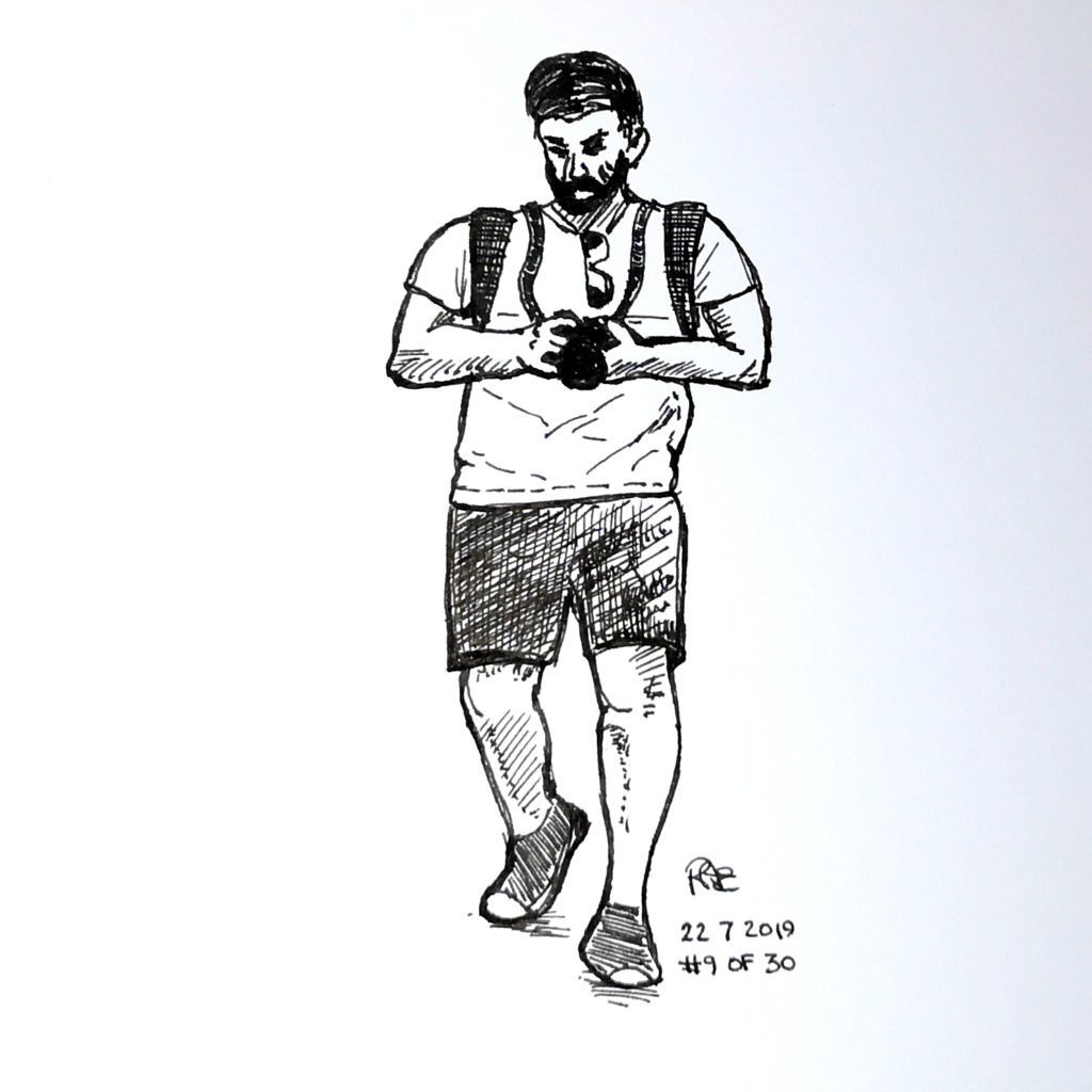 A pen and ink sketch of a man checking his camera